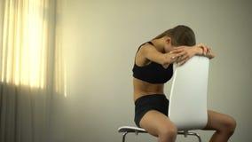 Muchacha flaca que se sienta en la silla, agotada por la desnutrición, anorexia, depresión almacen de metraje de vídeo