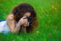 Muchacha-fotógrafo con el pelo rizado que miente en la hierba en el parque, sosteniendo una cámara y fotografiado la flor Fotos de archivo