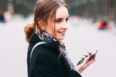 Muchacha franca sonriente con el teléfono en la calle Foto de archivo libre de regalías