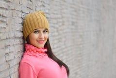 Muchacha fresca de la moda del retrato en ropa colorida sobre el fondo de madera que lleva un sombrero y un suéter rosado Imagenes de archivo