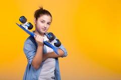 Muchacha fresca del adolescente con un monopatín azul en manos Fotos de archivo