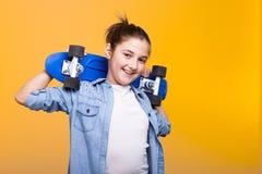 Muchacha fresca feliz del adolescente con un monopatín azul en manos Fotos de archivo libres de regalías