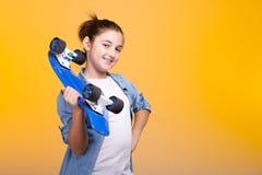 Muchacha fresca feliz del adolescente con un monopatín azul en manos Imágenes de archivo libres de regalías