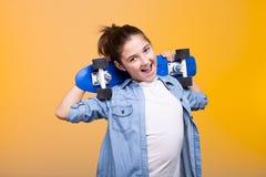 Muchacha fresca feliz del adolescente con un monopatín azul en manos Imagen de archivo