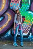 Muchacha fresca hermosa en sombrero y gafas de sol sobre la pared de la pintada Imagen de archivo