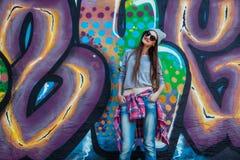 Muchacha fresca hermosa en sombrero y gafas de sol sobre la pared de la pintada Fotografía de archivo