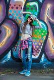 Muchacha fresca hermosa en sombrero y gafas de sol sobre la pared de la pintada Imágenes de archivo libres de regalías