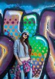 Muchacha fresca hermosa en sombrero y gafas de sol sobre la pared de la pintada Imagenes de archivo