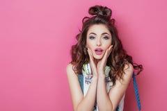 Muchacha fresca sorprendida de la moda bonita con los auriculares que llevan la ropa colorida con miradas del pelo rizado aislada Fotos de archivo