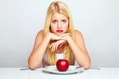 Muchacha frustrada con la manzana roja Fotos de archivo libres de regalías