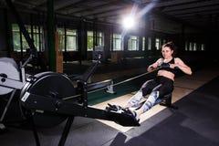 Muchacha fuerte joven que hace un ejercicio en un aparato de remar Para entrenar a los brazos cardiios, trasero Conceptos que se  foto de archivo