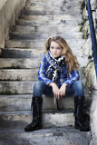 Muchacha fuerte sola que se sienta en escalera Imagen de archivo