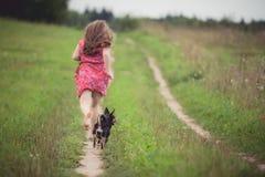 Muchacha funcionada con con el perro Fotos de archivo libres de regalías