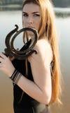 Muchacha gótica con el pelo rojo largo y el espejo viejo Foto de archivo