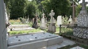 Muchacha gótica fúnebre que camina al lado de las piedras sepulcrales en un cementerio antiguo que comtempla muerte y soledad metrajes