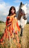 Muchacha gitana con un caballo gris Foto de archivo