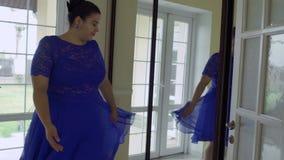 Muchacha gorda en un vestido azul delante de un espejo almacen de metraje de vídeo
