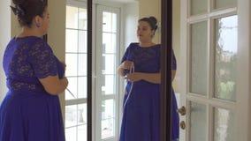 Muchacha gorda en un vestido azul delante de un espejo metrajes