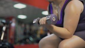Muchacha gorda que ejercita con pesa de gimnasia en el gimnasio, trabajando difícilmente para perder el exceso de peso almacen de video