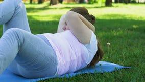 Muchacha gorda que hace apenas el pectoral, mintiendo en la estera en parque, entrenamiento agotado, adietando almacen de metraje de vídeo