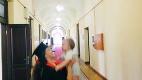 Muchacha graduada con su niño en el pasillo de la universidad metrajes
