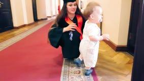 Muchacha graduada con su niño en el pasillo de la universidad almacen de video