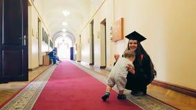 Muchacha graduada con su niño en el pasillo de la universidad almacen de metraje de vídeo