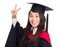 Muchacha graduada del asiático con la muestra de la victoria Imagen de archivo libre de regalías