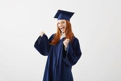 Muchacha graduada feliz en la sonrisa de risa del júbilo de la capa sobre el fondo blanco Fotos de archivo libres de regalías