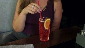 Muchacha grasa feliz joven que se sienta en café en verano con limonada fría almacen de video