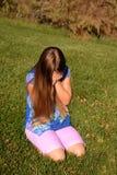 Muchacha gritadora que se sienta en la hierba Foto de archivo libre de regalías