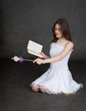 Muchacha - hada con la varita y el libro mágicos en manos Fotos de archivo
