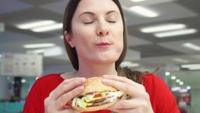 Muchacha hambrienta que come la hamburguesa en la zona de restaurantes Cheeseburger penetrante de la mujer en el restaurante de l almacen de video