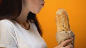 Muchacha hambrienta que muerde el pan, la fibra y el gluten recientemente cocidos en el pan, atención sanitaria almacen de video