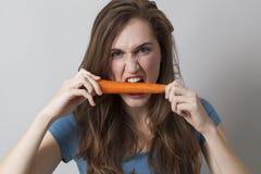 Muchacha hambrienta 20s que muerde una zanahoria con apetito foto de archivo