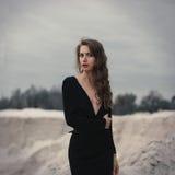 Muchacha hermosa adentro en vestido negro del vintage con el pelo rizado que presenta en la arena Mujer en dres retros Emoción se imágenes de archivo libres de regalías