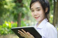 Muchacha hermosa adolescente del estudiante tailandés que usa su tableta que se sienta en parque Imagen de archivo libre de regalías
