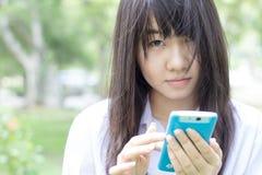 Muchacha hermosa adolescente del estudiante tailandés que usa su teléfono elegante que se sienta en parque Foto de archivo