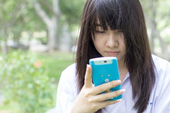 Muchacha hermosa adolescente del estudiante tailandés que usa su teléfono elegante que se sienta en parque Fotos de archivo