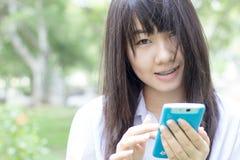 Muchacha hermosa adolescente del estudiante tailandés que usa su teléfono elegante que se sienta en parque Foto de archivo libre de regalías