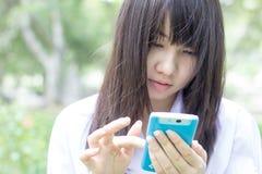 Muchacha hermosa adolescente del estudiante tailandés que usa su teléfono elegante que se sienta en parque Imagen de archivo libre de regalías