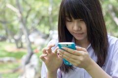 Muchacha hermosa adolescente del estudiante tailandés que usa su teléfono elegante que se sienta en parque Imagenes de archivo