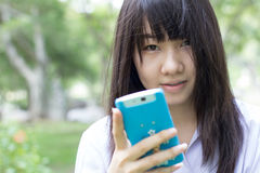 Muchacha hermosa adolescente del estudiante tailandés que usa su teléfono elegante que se sienta en parque Imágenes de archivo libres de regalías