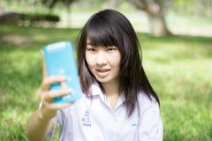 Muchacha hermosa adolescente del estudiante tailandés que usa su teléfono elegante Selfie en parque Imagen de archivo libre de regalías