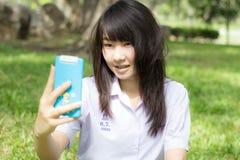 Muchacha hermosa adolescente del estudiante tailandés que usa su teléfono elegante Selfie en parque Fotografía de archivo libre de regalías