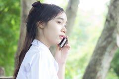 Muchacha hermosa adolescente del estudiante tailandés que usa su teléfono y sonrisa Foto de archivo