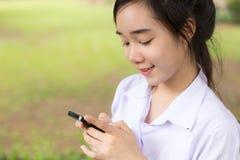 Muchacha hermosa adolescente del estudiante tailandés que usa su teléfono y sonrisa Imagen de archivo libre de regalías