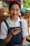 Muchacha hermosa adolescente del estudiante tailandés que usa su teléfono y sonrisa elegantes Imagen de archivo libre de regalías