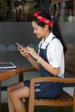 Muchacha hermosa adolescente del estudiante tailandés que usa su teléfono y sonrisa elegantes Foto de archivo