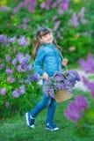 Muchacha hermosa adorable linda de la mujer de la señora con el pelo moreno en un prado del arbusto de la púrpura de la lila Gent Fotos de archivo